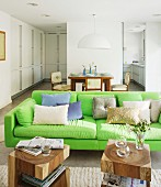 Neon-green sofa and solid wooden side table in open-plan interior