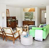 Offener Wohnbereich mit neongrünem Sofa, Armlehnstüheln und Antikmöbeln