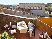Sunny seating area on terrace with view across Mediterranean roofs