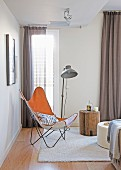 Butterfly-Chair und Stehleuchte neben Baumstamm-Hocker