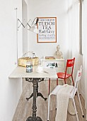 Bistro table with marble top and cast iron frame and two chairs in narrow room