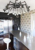 Elegant kitchen island below designer lamp with multiple anglepoise arms