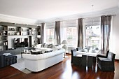 White sofa set, shelving, dining table and grey loose-covered chairs in elegant lounge area