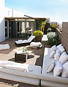 Elegant lounger and benches with white cushions on sunny roof terrace