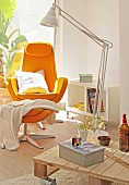Orange armchair with footstool and standard lamp in front of low coffee table on castors