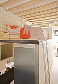 Cube containing bathroom with bed and bedside cabinet on top in sleeping area accessed by metal ladder in loft apartment