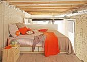 Schlafebene mit orangefarbenen Akzenten in Loftwohnung unter sichtbaren Balken und Lüftungsrohr