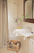 Bathroom utensils in wooden crate on castors in bathroom in shades of brown