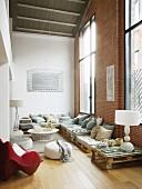 Lounge mit Palettenmöbeln in Loftwohnung mit Ziegelwand