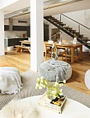 Long dining table and kitchen counter below steel staircase in loft apartment with lounge area in foreground