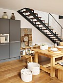 Solid wooden furniture in dining area of open-plan kitchen next to steel staircase