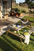 Wooden picnic table and benches in garden outside house