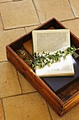 Open book and leafy branch in wooden box on floor