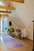 Hammock, houseplant and ethnic mask in high-ceilinged attic room