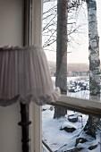 Lampe am Fenster, Blick auf verschneite Landschaft mit Bäumen