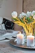 Zwei brennende Kerzen auf einem Tablett mit einem Strauß Tulpen