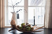 Pears and green apples on antlers in front of window