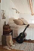 Schwarze Gitarre lehnt am Bett im ländlich romantischen Schlafzimmer