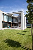Modern architect-designed house with flat roof, glass façade, roofed terrace and manicured lawn
