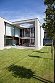 Modernes Architektenhaus mit Flachdach, Glasfassade, überdachter Terrasse und gepflegtem Rasen