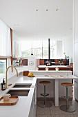 Designer kitchen with breakfast bar in open-plan interior
