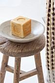 Seife in Seifenschale auf rustikalem Holzhocker