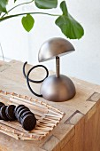 Cookies in bamboo basket and metal table lamp on wooden cube