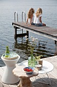 Drinks, flowers and fruit on three side tables next to lake with two girls sat on jetty in background