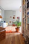 Raumhohes Bücherregal und Korbtruhe im Vorraum, wohnliches Badezimmer mit Zimmerpflanze auf Teppich, Badewanne und hellgrauer Wand