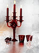 Red glass candelabra and baubles against silver wall