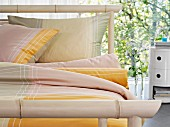 Bamboo bed and yellow bed linen in front of glass wall