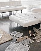 weiße Sofas mit Klappfunktion auf Betonboden mit Zeitungen
