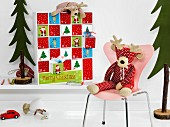 Fabric moose on chair in front of Advent calender with drawers