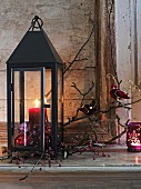 Lantern festively decorated with candle, twigs and pink accessories