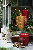 Gold and red candles in lantern decorated with green twigs
