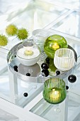 White and green tealight holders on silver tray