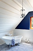 Free-standing bathtub and blue accent wall in attic bathroom