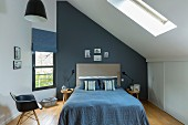 Double bed with blue cover in attic room