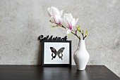 Magnolienblüte in weisser Vase vor Bild mit Schmetterlingsmotiv an Betonwand