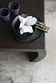 White magnolia flower in black bowl, silver cutlery and black tealight holders on table