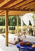 Überdachter Terrassenplatz mit Holzliegestuhl, Palettentisch und Bodenkissen