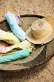 Rolled towels and straw hat in woven basket with ethnic pattern