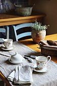 Table set for two with runner, floral teacups, white butter dish and basket of bread