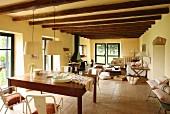 Blick über Esstisch in offenen Wohnbereich mit Kaminofen und Holzbalkendecke in renoviertem Landhaus
