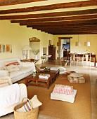 Offener Wohnbereich in renoviertem Landhaus mit Holzbalkendecke und weißem Polstersofa
