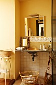 Bathroom accessories on vintage washstand with tiled dado rail and mirror