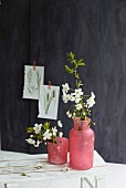 Flowering branches in red vase against black wall