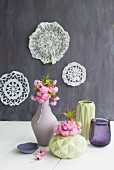 Flowering branches in vases with structured surfaces and lace doilies on wall