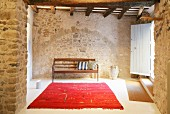 Red rug and wooden bench in foyer of restored stone house