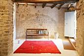 Restauriertes Natursteinhaus mit rotem Teppich und Holzbank im Eingangsbereich